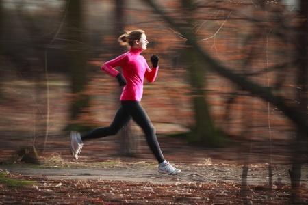 personas corriendo: Mujer joven correr al aire libre en un parque de la ciudad en una fr�a de oto�o  invierno d�a (movimiento de la imagen borrosa)