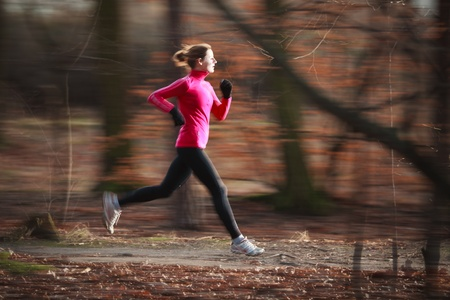 Young woman running outdoors in a city park on a cold fall/winter day (motion blurred image) photo