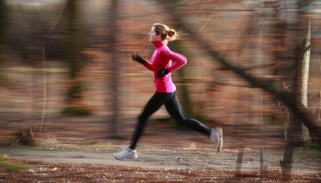 course � pied: Jeune femme courir en plein air dans un parc urbain sur une froide automne  hiver jour (image floue de mouvement)