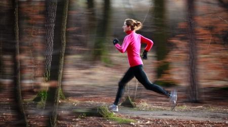 coureur: Jeune femme en cours d'ex�cution � l'ext�rieur dans un parc de la ville par un froid d'automne  hiver jour (image en mouvement floue)