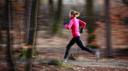 nina corriendo: Mujer joven correr al aire libre en un parque de la ciudad en una fría de otoño  invierno día (movimiento de la imagen borrosa)