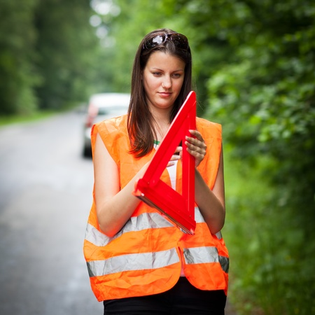 Young female driver wearing a high visibility vest, calling the roadside serviceassistance after her car has broken down photo