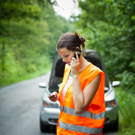 warning triangle: Young female driver wearing a high visibility vest, calling the roadside serviceassistance after her car has broken down Stock Photo