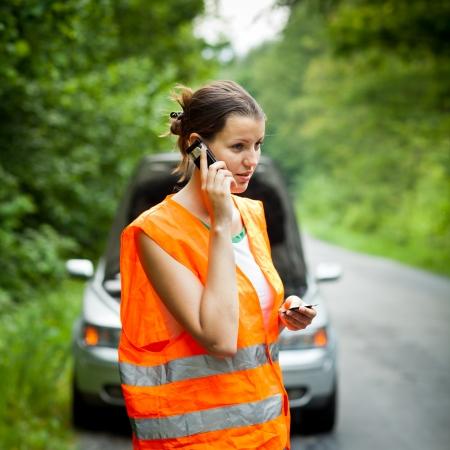 zichtbaarheid: Jonge vrouwelijke bestuurder het dragen van een hoge zichtbaarheid vest, het aanroepen van de roadside service  hulp nadat haar auto is opgesplitst
