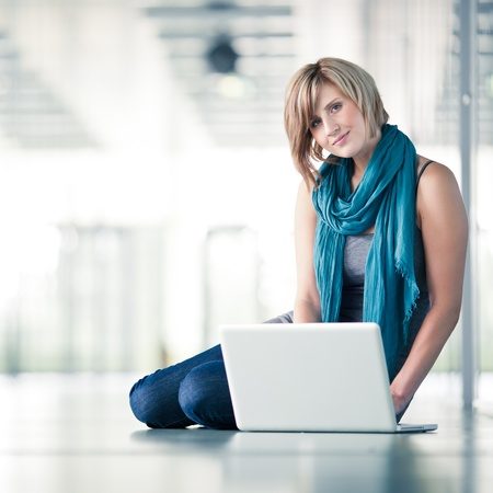 student: Pretty young female student with a laptop computer on collegeuniversity campus (shallow DOF; color toned image) Stock Photo