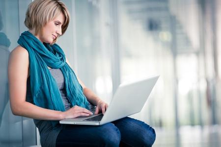 Mooie jonge vrouwelijke student met een laptop op school / campus van de universiteit (ondiepe DOF, kleur getinte afbeelding)