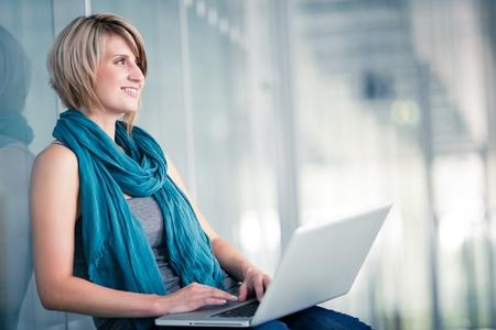 Mooie jonge vrouwelijke student met een laptop computer op college  campus van de universiteit (ondiepe DOF, kleuren getinte afbeelding)