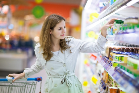 grocery cart: Beautiful young woman shopping for fruits and vegetables in produce department of a grocery storesupermarket Stock Photo
