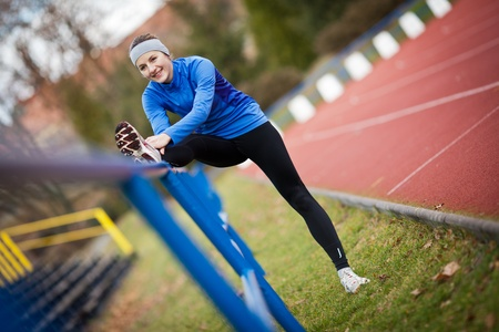 jogging track: Young woman stretching before her run Stock Photo