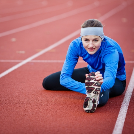 Young woman stretching before her run photo