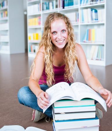 pretty female college student in a library  photo