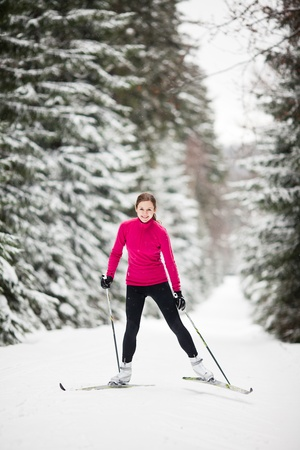 Cross-country skiing: young woman cross-country skiing on a lovely sunny winter day photo