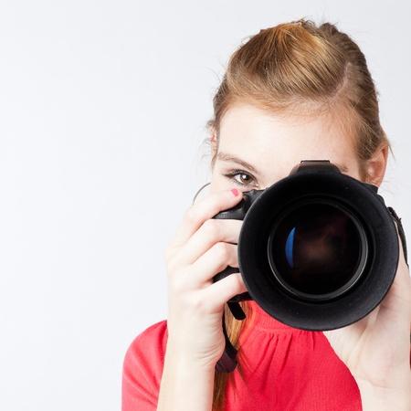 color digital camera: pretty, female photographer with her digital camera (color toned image; shallow DOF)