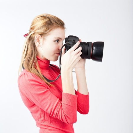 photographing: pretty, female photographer with her digital camera (color toned image; shallow DOF)