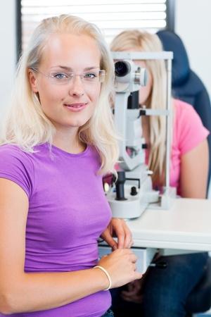 oculista: concepto de la optometría - Retrato de un optometrista bastante joven con lámpara de hendidura, control de la vista de su paciente (imagen a color entonado) Foto de archivo