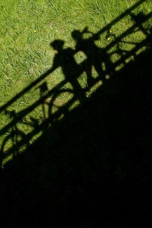 halt: two mountain bikers silhouettes during a halt on a bridge Stock Photo