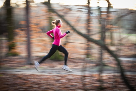 young woman running: Young woman running outdoors in a city park on a cold fallwinter day (motion blurred image) Stock Photo