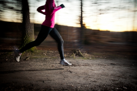 runner girl: Young woman running outdoors in a city park on a cold fallwinter day (motion blurred image) Stock Photo