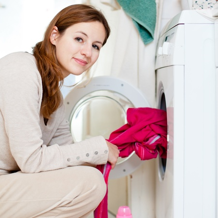 Housework: young woman doing laundry (shallow DOF; color toned image) Stock Photo