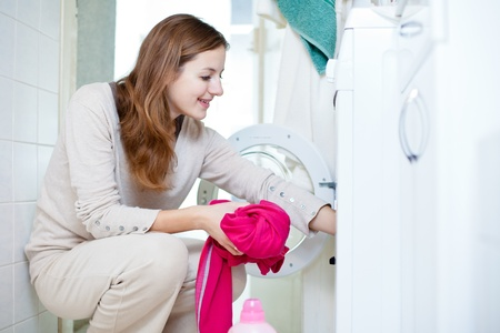 Housework: young woman doing laundry (shallow DOF; color toned image) Stock Photo - 12115918