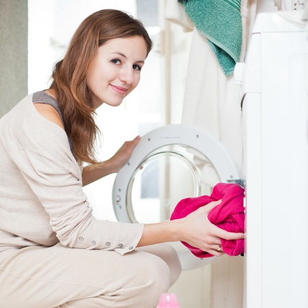 bright housekeeping: Housework: young woman doing laundry (shallow DOF; color toned image) Stock Photo
