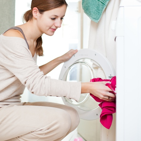laundry: Housework: young woman doing laundry (shallow DOF; color toned image) Stock Photo