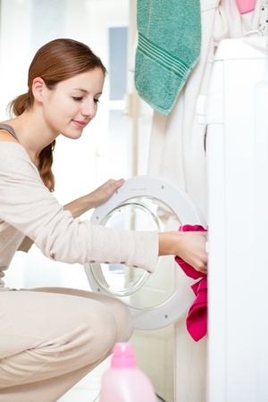 Housework: young woman doing laundry (shallow DOF; color toned image) Stock Photo - 12115872