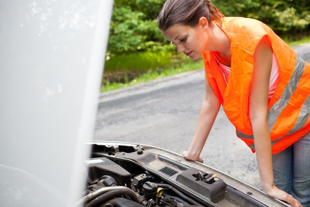 Young female driver wearing a high visibility vest, bending over the engine of her broken down car photo
