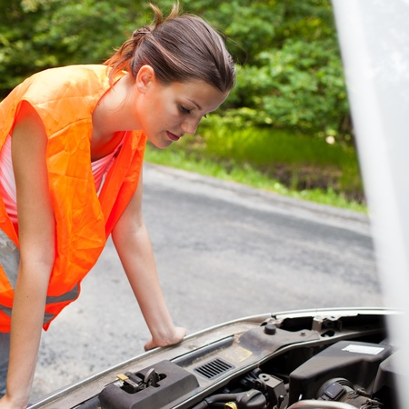 Young female driver wearing a high visibility vest, bending over the engine of her broken down car Stock Photo - 12115908