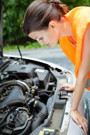 zichtbaarheid: Jonge vrouwelijke chauffeur het dragen van een hoge zichtbaarheid vest, buigen over de motor van haar kapotte auto