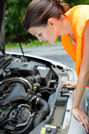 high visibility: Young female driver wearing a high visibility vest, bending over the engine of her broken down car Stock Photo