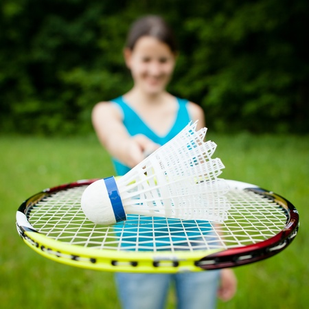 Pretty, young woman playing badminton in a city park on a lovely summer day (shallow DOF) photo