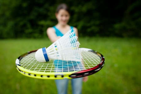badminton: Pretty, young woman playing badminton in a city park on a lovely summer day (shallow DOF) Stock Photo
