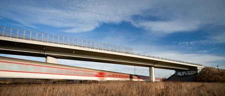 Fast train passing under a bridge on a lovely summer day (motion blurred image) photo
