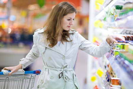 produce sections: Beautiful young woman shopping for fruits and vegetables in produce department of a grocery storesupermarket Stock Photo