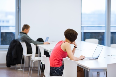 Pretty young college student studying in the librarya study room at campus (shallow DOF) photo