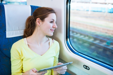 Young woman using her tablet computer while traveling by train photo