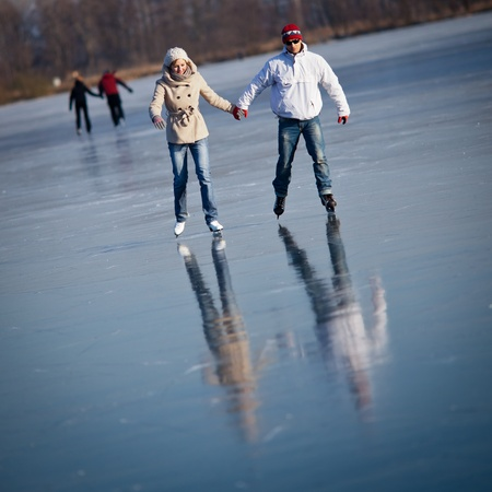 Couple ice skating outdoors on a pond on a lovely sunny winter day photo