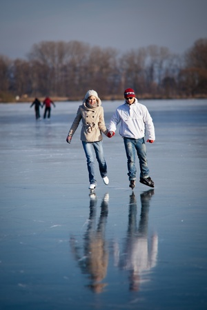 rink: Couple ice skating outdoors on a pond on a lovely sunny winter day Stock Photo