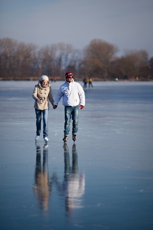 Couple ice skating outdoors on a pond on a lovely sunny winter day Stock Photo - 12405578