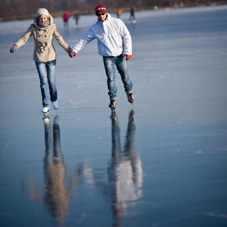 patinaje sobre hielo: Pareja de patinaje de hielo al aire libre en un estanque en un día soleado de invierno preciosa Foto de archivo