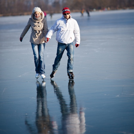 Couple ice skating outdoors on a pond on a lovely sunny winter day Stock Photo - 12405557