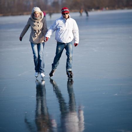 patinaje: Pareja de patinaje de hielo al aire libre en un estanque en un día soleado de invierno preciosa Foto de archivo