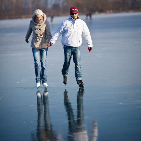 skating rink: Couple ice skating outdoors on a pond on a lovely sunny winter day Stock Photo
