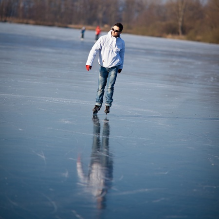 Handsome young man ice skating outdoors on a pond (color toned image; shallow DOF) photo