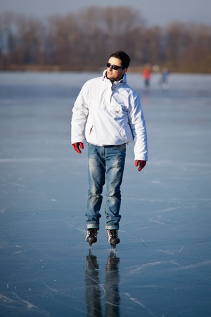 Handsome young man ice skating outdoors on a pond (color toned image; shallow DOF) Stock Photo - 12405579