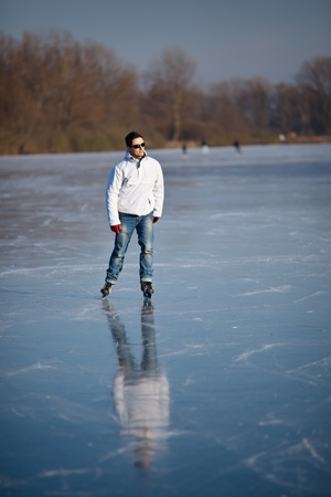 Handsome young man ice skating outdoors on a pond (color toned image; shallow DOF) Stock Photo - 12405576