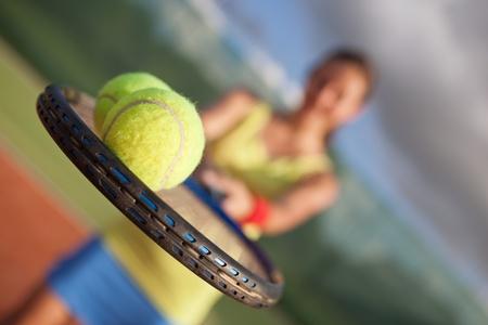 jugando tenis: bastante, joven jugador de tenis femenino en la pista de tenis (DOF bajo el foco, selectivo) Foto de archivo