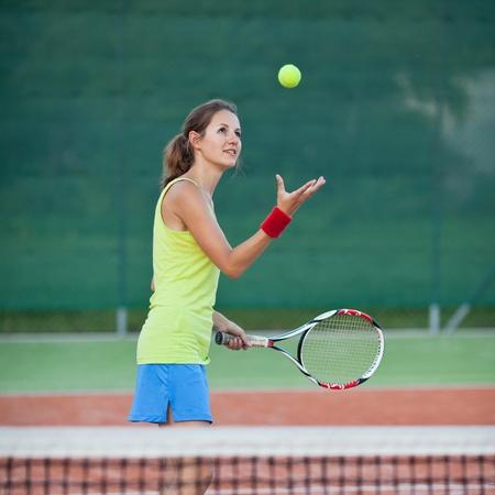 jugando tenis: bonita, joven jugador de tenis femenino en la cancha de tenis (DOF bajo el foco, selectivo) Foto de archivo