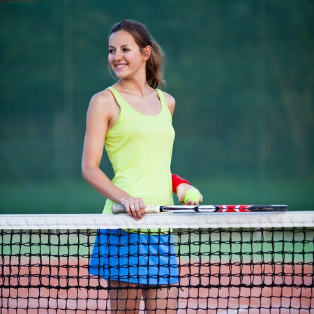 pretty, young female tennis player on the tennis court (shallow DOF, selective focus) photo